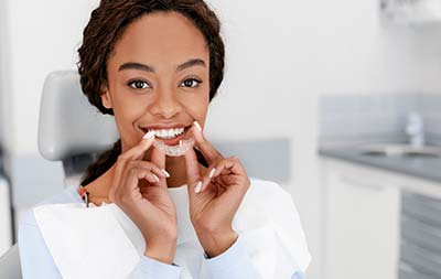 woman holding her Invisalign clear aligners